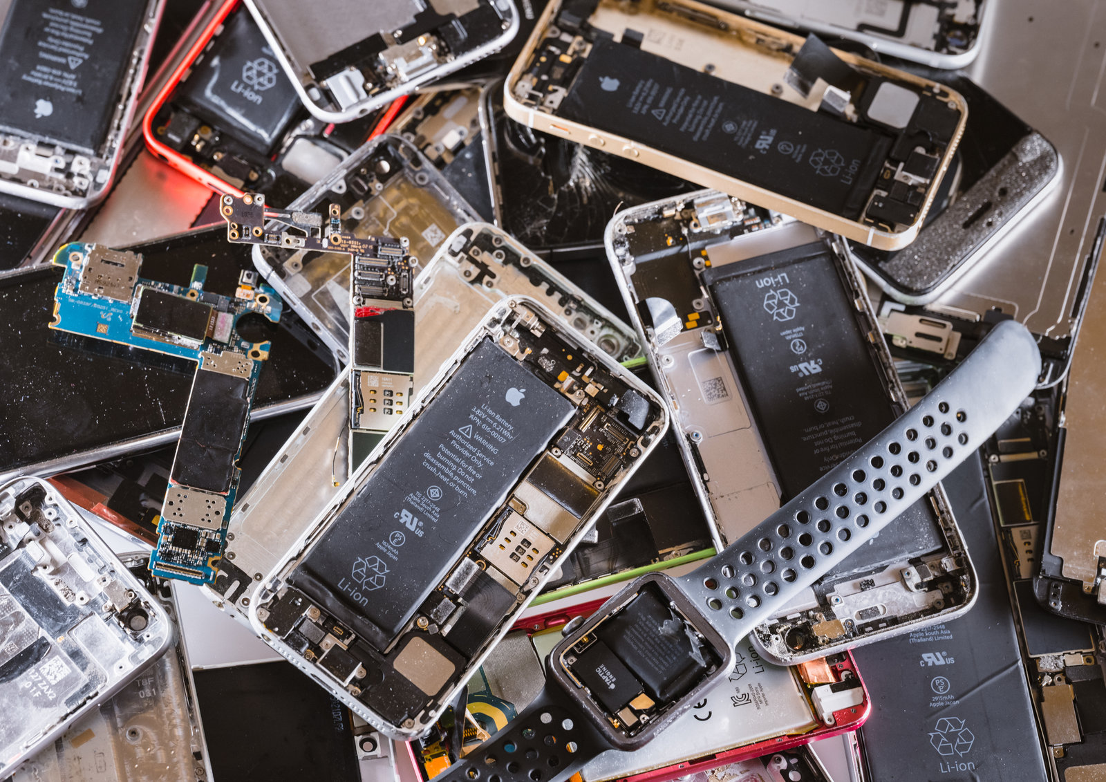 A pile of mobile phones and smart watches with their back covers removed